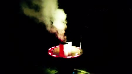 atmosféra : Incredible aerial drone 4k view on energy power station tower producing bright coloured smoke in dark black night sky