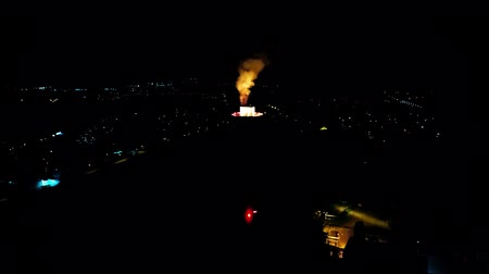 atmosféra : Wonderful aerial drone 4k view on energy power station tower producing bright coloured smoke in dark black night sky