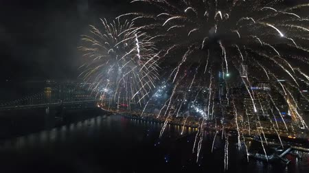 celebration : Amazing colorful fireworks exploding in dark night sky in bright illumination cityscape skyline background Wideo