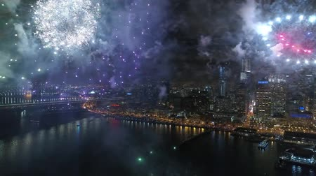 új év : Incredible colorful fireworks explosion in dark night sky in bright illumination cityscape skyline background