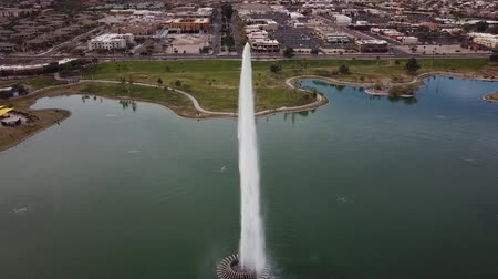 géiser : Incredible aerial drone 4k view on huge tall fountain spraying water high up in sky in small lake in middle of city Vídeos