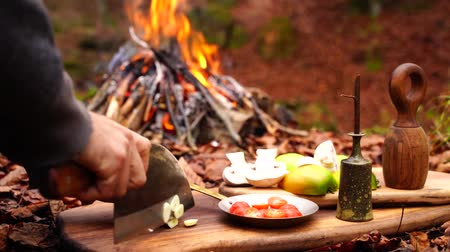 wołowina : Man hands cutting slicing garlic vegetable with big cooking axe knife on wooden board on forest camp fire background