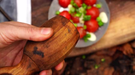 požár : Close up view on man hand putting pepper into fresh cut vegetable bowl salad tomato pepper onion on wood board in forest