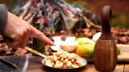 wołowina : Man hand puttingcanned haricot beans into fresh cut vegetable bowl salad tomato pepper onion on wood board in camp fire Wideo