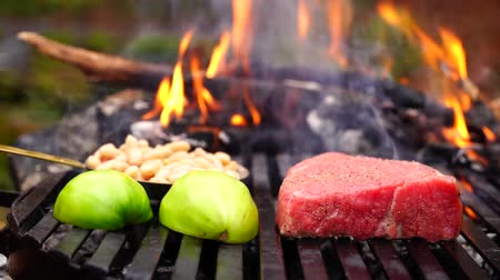 wołowina : Man hand puts fresh cut vegetables on black grill pan with big piece of beef steak pink meat in forest camp fire flame