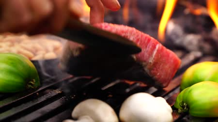 grillowanie : Man hand rotating big piece of beef steak pink meat on grill pan with fresh cut vegetable with in forest camp fire flame