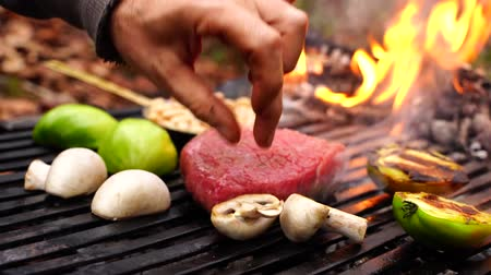wołowina : Man hand turning over fresh cut vegetables big piece of beef steak pink meat on grill pan in forest camp fire flame Wideo