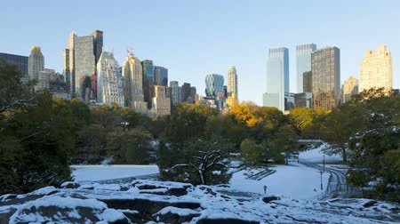 states : Amazing morning to day time lapse view on snow covered Central Park in middle of Manhattan downtown New York cityscape