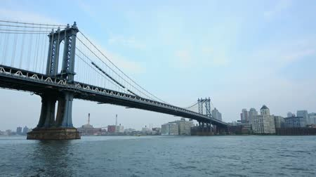 baixo ângulo : Fascinating time lapse low angle view on Brooklyn Bridge on cloudy day in New York Manhattan downtown cityscape seascape