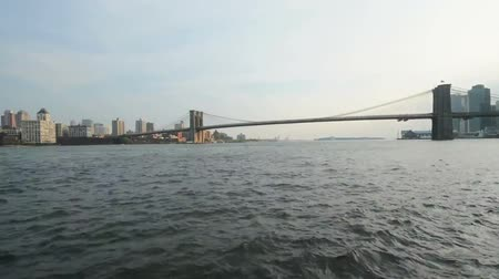 semt : Fast low angle time lapse view on calm ocean water moving in small waves with Brooklyn bridge in background New York
