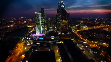 felhőkarcolók : Stunning aerial drone view on bright evening night Moscow city illumination in busy metropolis downtown cityscape
