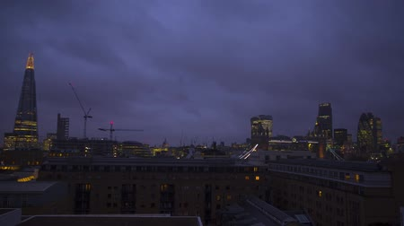 crepúsculo : Wonderful time lapse steady shot of heavy rain clouds moving fast in dark night sky over modern downtown London rooftops