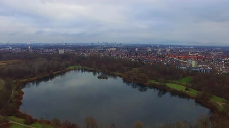 旅行の目的地 : Fascinating aerial 4k drone flight over calm small city cityscape with big mirror surface lake in park on cloudy day