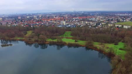 небольшой : Gorgeous aerial 4k drone flight over calm small city cityscape with big mirror surface lake in park on cloudy day