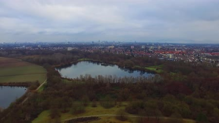 alto : Picturesque aerial 4k drone flight over calm small city cityscape with big mirror surface lake in park on cloudy day