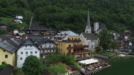 hallstatter see : Stunning 4k aerial drone flyover in cloudy sky over small cozy houses on mountain lake beach in Austria forest landscape Stock Footage