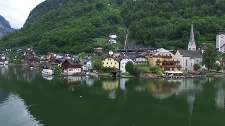 hallstatter see : Impressive 4k drone aerial flight over ancient house mirror surface lake beach in wild nature mountain forest landscape