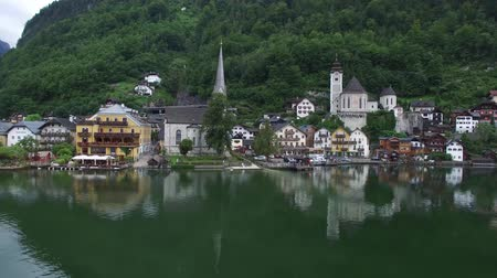 hallstatter see : Wonderful 4k drone aerial flight over ancient house mirror surface lake beach in wild nature mountain forest landscape