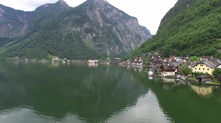 hallstatter see : Beautiful 4k drone aerial flight over ancient house mirror surface lake beach in wild nature mountain forest landscape