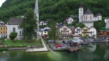 hallstatter see : Aerial drone 4k panorama flyover in Austria small cozy house village on lake beach in amazing mountain forest landscape