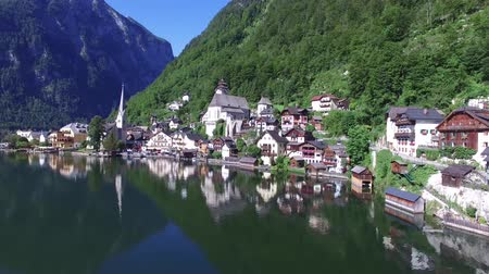 hallstatter see : Stunning 4k aerial drone panorama flight over small house Austria village in wild nature forest mountain lake landscape