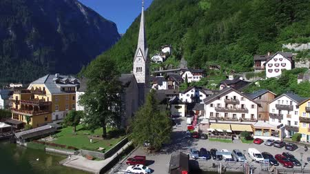 hallstatter see : Aerial drone 4k panorama flyover in Austria small cozy house village on lake beach in gorgeous mountain forest landscape Stock Footage