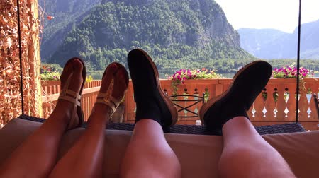 erkély : First person shot of romantic couple legs swinging on cozy flowers balcony swing in sunny mountain forest lake landscape Stock mozgókép