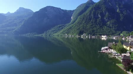 hallstatter see : Fascinating 4k aerial drone panorama shot of mirror surface lake water in middle of Austrian pine tree forest mountains