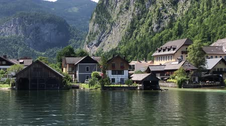 à beira do lago : Gorgeous 4k panorama view on cozy villa house in small Austrian village by lake pine tree wild nature mountain landscape Stock Footage