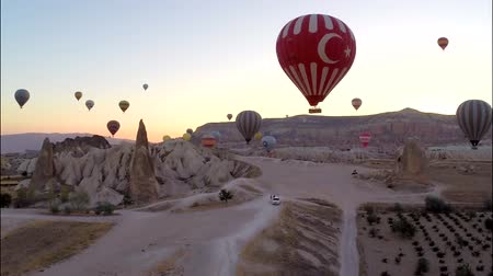 リフト : Fascinating aerial panorama view on huge hot air balloons flying high in evening sunset sky over rock sand stone desert