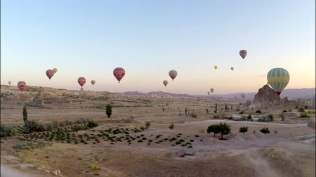 balão : Magnificent aerial panorama view on huge hot air balloons flying high in evening sunset sky over rock sand stone desert