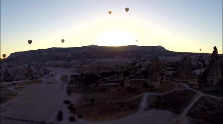 globos : Spectacular aerial panorama view on huge hot air balloons flying high in evening sunset sky over rock sand stone desert