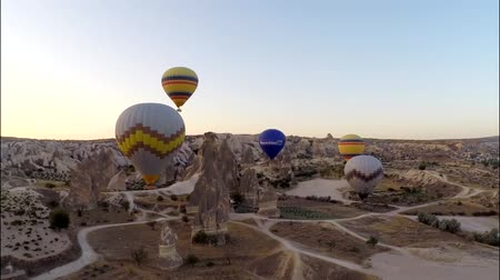 air vehicle : Picturesque aerial panorama view on colorful hot air balloons flying high in evening sunset sky over stone rock desert