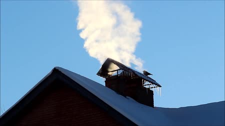 The smoke from the chimney of a private house on a background of blue sky