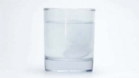 Effervescent aspirin melts in a glass of water on a white background.