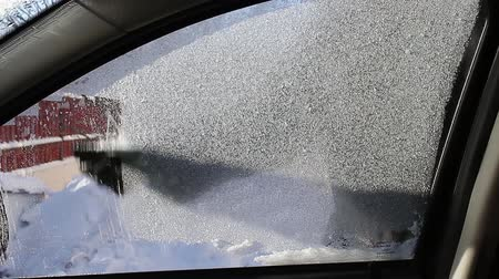 Cleaning the side car windows of ice before the trip.