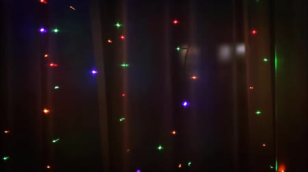 Christmas lights in the window on the background of transparent tulle. Стоковые видеозаписи