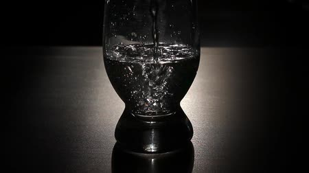 Water is poured into a glass close-up on a dark background.