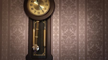 Antique wall clock with a pendulum closeup.