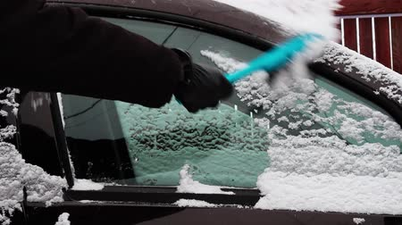 Cleaning the car window from the snow.