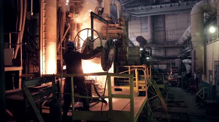 open hearth : Worker on steel plant operates with  molten metal.