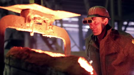 çinko : Worker on steel plant operates with  molten metal.