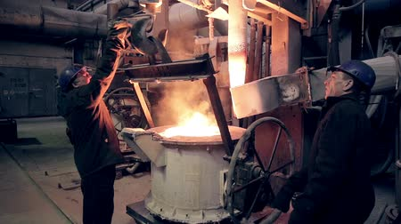 open hearth : Worker on steel plant operates with liquid metal.