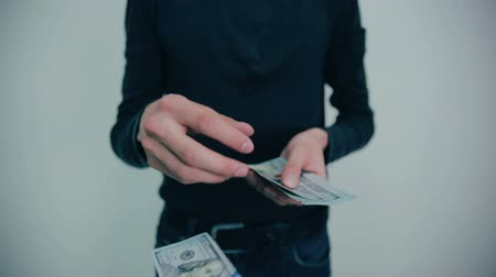 финансы : Young man throws money to camera. Dollars.