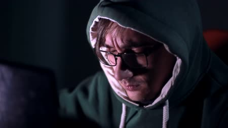 хакер : Male hacker works on a computer with data on screens in a dark room.