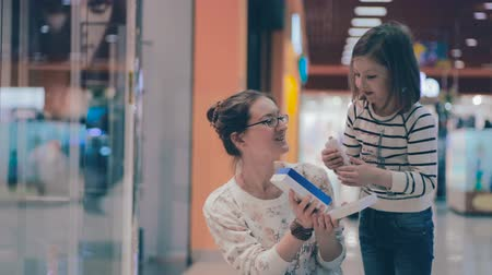 vzrušený : Mother shows daughter a gift box just baught at mall. Being excited about shopping sales.