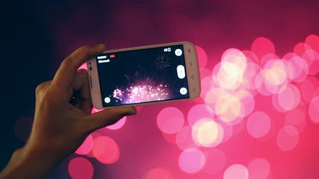 esemény : Man filming colorful fireworks on his cell phone.