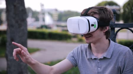fejhallgató : Young handsome man wearing virtual reality goggles sitting in a city park. Stock mozgókép