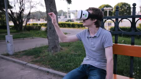 simülasyon : Young handsome man wearing virtual reality goggles sitting in a city park. Stok Video
