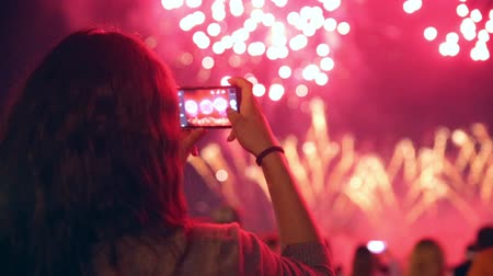 июль : Unrecognizable woman filming colorful fireworks on his cell phone.